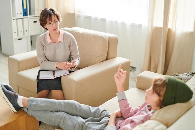 Агрессивный мальчик показывает средний палец школьному психологу