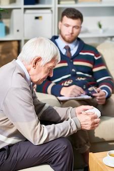 Старший мужчина рассказывает о своих страхах с психиатром