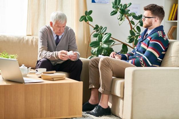 Серьезный старший мужчина с салфеткой делится своими страданиями со святыней