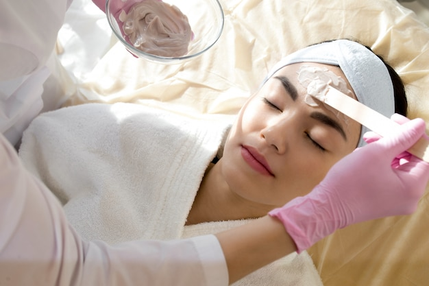 美容師がフェイスマスクのクローズアップを適用します。