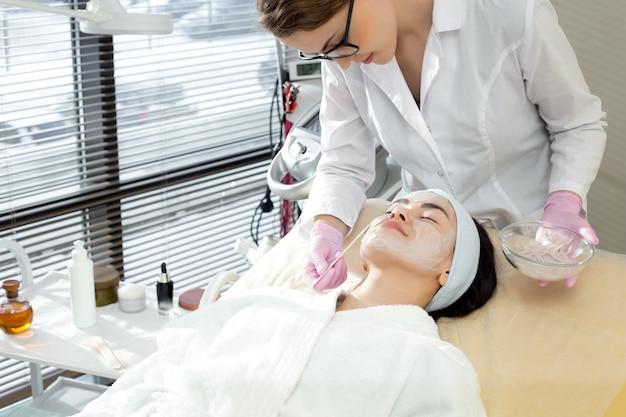 フェイスマスクを適用する女性美容師