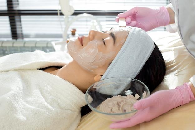美容師はフェイスマスクの側面図を適用します