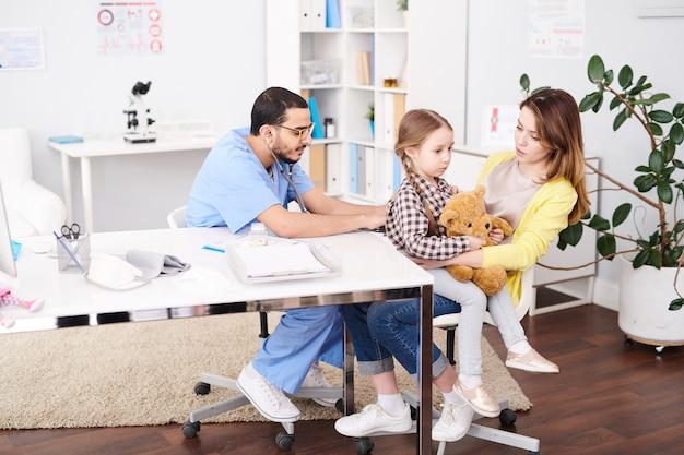 小児科医が小さな子供を調べる