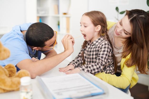 小児科医が子供の喉を調べる