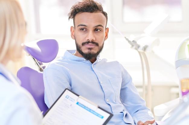歯科用椅子に座っている現代の若い男
