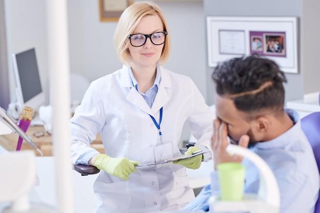 患者に耳を傾けるフレンドリーな女性歯科医