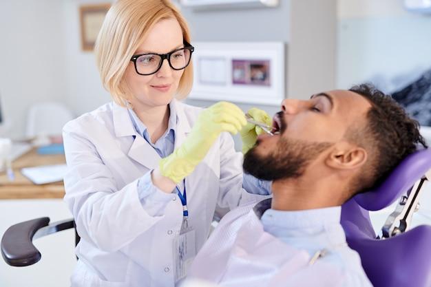 金髪の女性歯科医が患者と一緒に働く