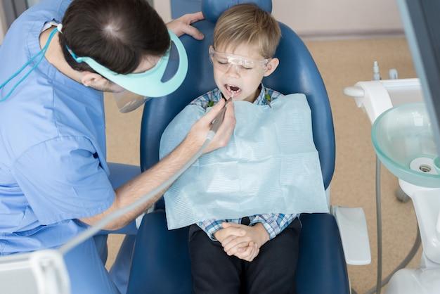歯科医は小さな男の子を扱います