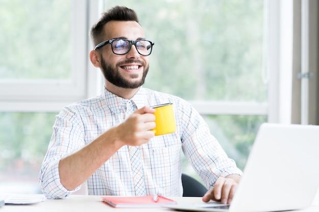 ハンサムな起業家が働くオフィスを楽しんでいます
