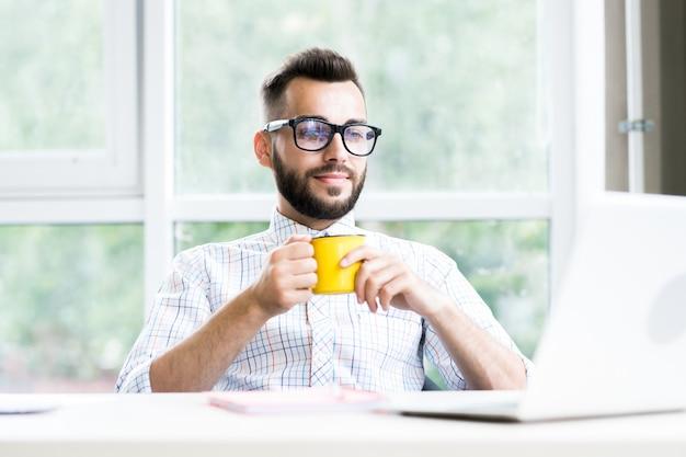 成功した起業家がオフィスでコーヒーを飲む