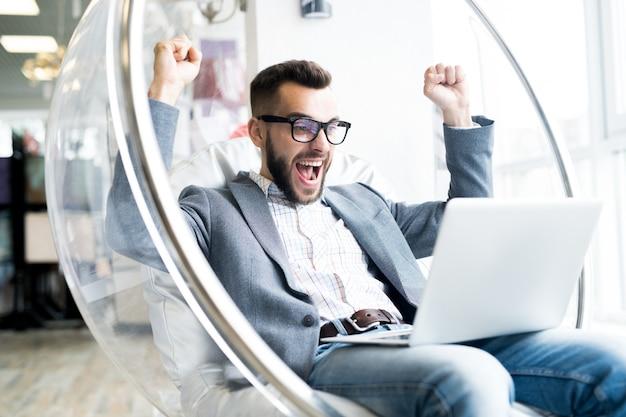 Возбужденный бизнесмен, используя ноутбук