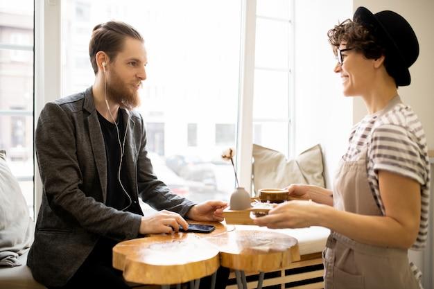 Положительная официантка, дающая поднос с кофе клиенту