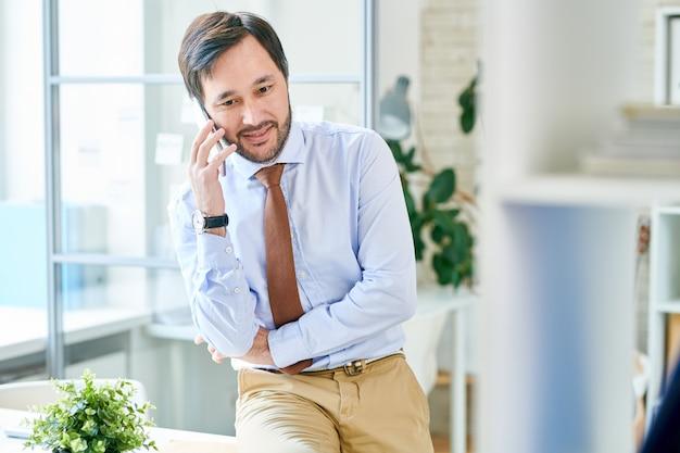Довольный бизнесмен, имеющий телефонный звонок