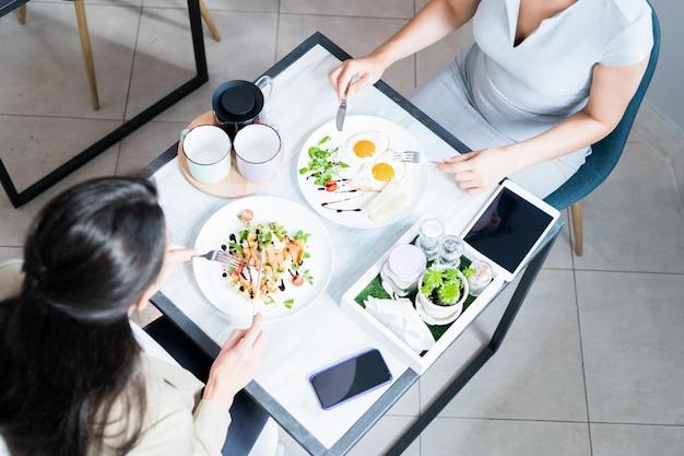 Две женщины наслаждаются едой в кафе