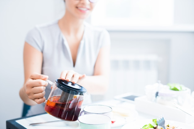 Молодая женщина наливает чай
