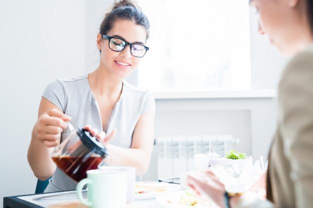 Молодая женщина наливает чай в кафе