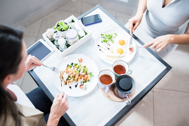 Две женщины наслаждаются завтраком