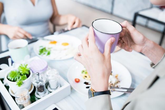 Женщина держит чашку в кафе