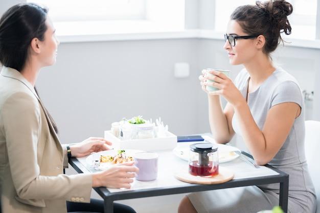 Две женщины общаются за столом в кафе