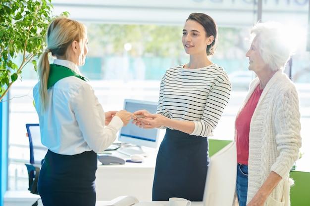 Специалист по банковскому обслуживанию клиентов дает деньги молодой леди с моли