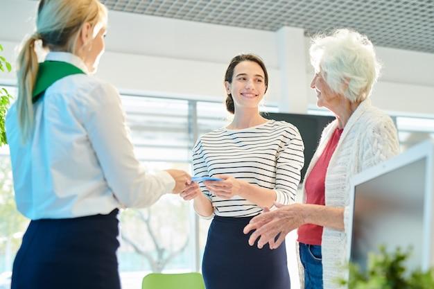 Сотрудник банка выдает документы молодой девушке с мамой