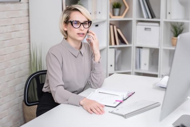 Женский менеджер разговаривает с клиентом по телефону