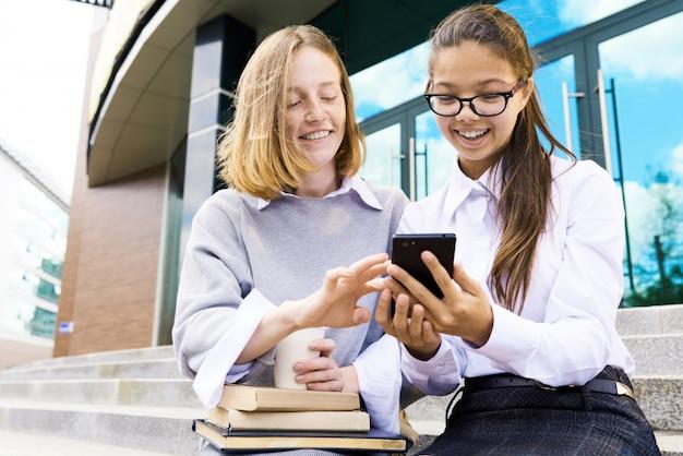 Веселые подростки вне школьного здания