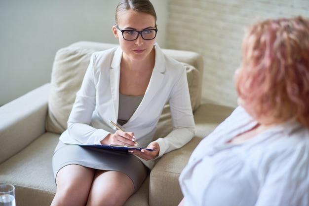 Женский психиатр, слушающий ожирение пациента