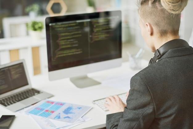創造的な若いウェブ開発者がコードを書く