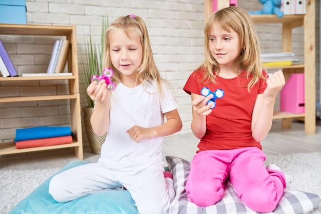 Маленькие девочки играют с непоседой спиннер