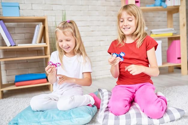 Маленькие сестры играют с популярными игрушками