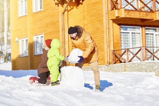 Семья строит снеговика