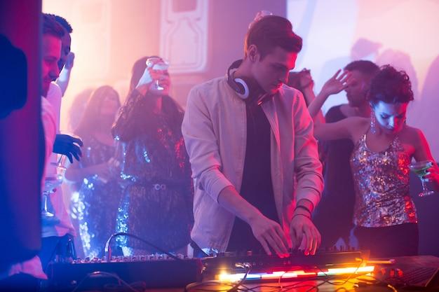 Молодой диджей играет в ночном клубе