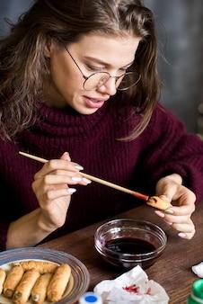 Позитивная леди, рисующая печенье хэллоуина