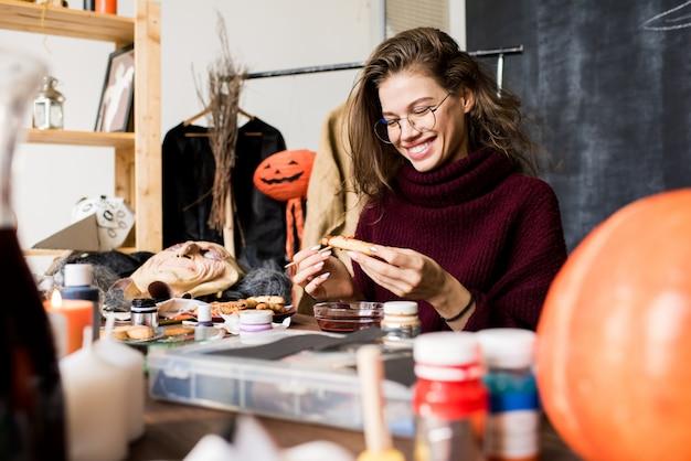 Взволнованная леди, делающая печенье хэллоуина более реалистичным