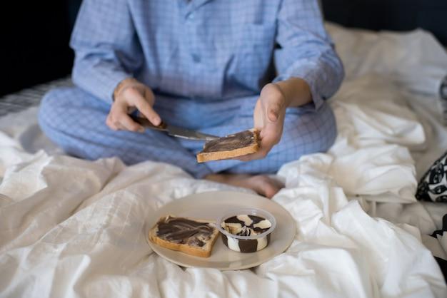 ベッドに座って朝食を持っているパジャマの男性
