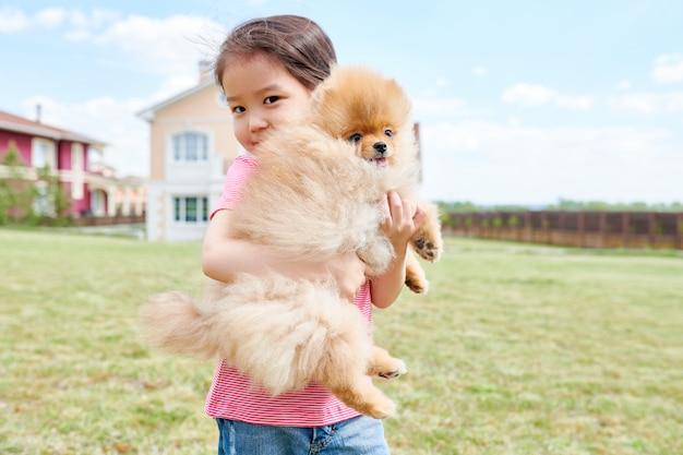 ペットの犬を保持しているアジアの女の子