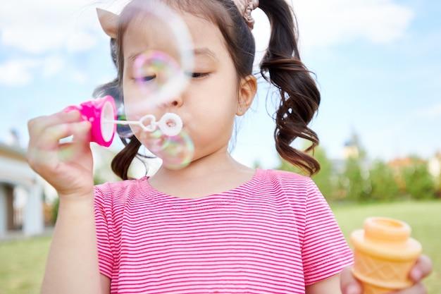 屋外で泡を吹いてかわいいアジアの女の子