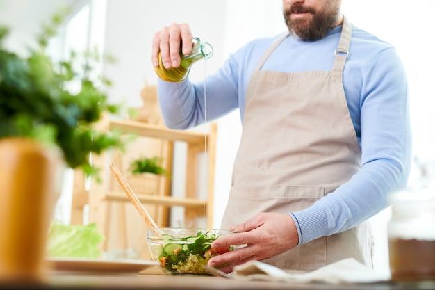 ひげを生やした男が野菜サラダを準備