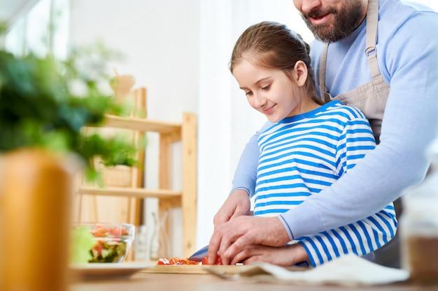 健康的な夕食を準備している父と娘