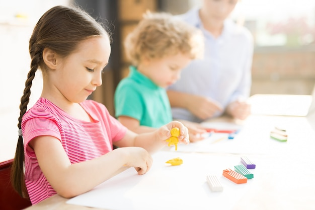 Маленькая девочка на уроке искусства и ремесла