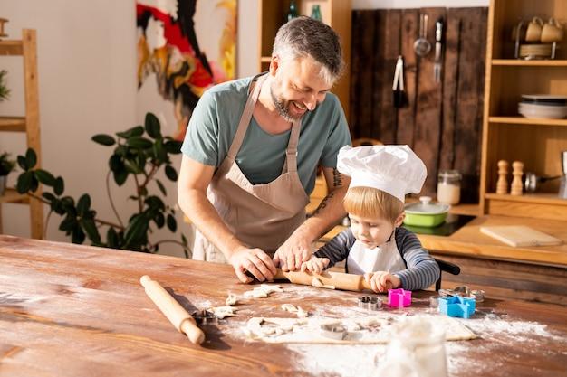 陽気な父親が息子に生地を転がすことを教える