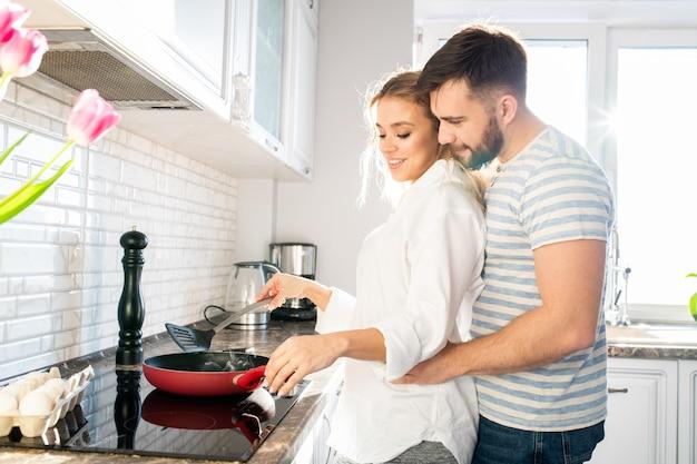 愛するカップルがキッチンで朝食を調理