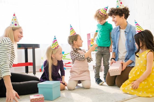 誕生日パーティーで子供たちと遊ぶ若い母親