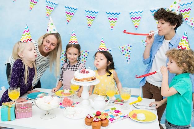 ケーキのろうそくを吹きかわいい女の子