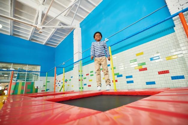 Афро-американский мальчик прыгает на батуте