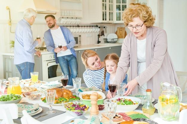 Большая счастливая семья готовит обеденный стол для вечеринки
