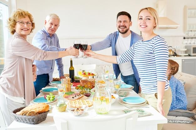 Семья позирует за обеденным столом во время празднования