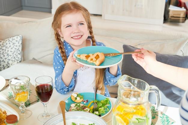 家族との夕食を楽しんでいるかわいい女の子