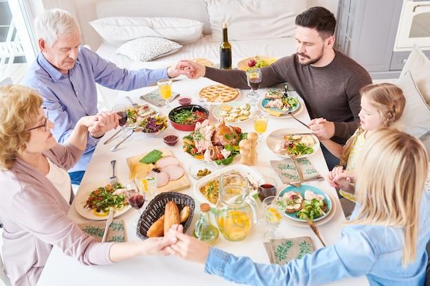 Большая семья говорит грейс на обеде